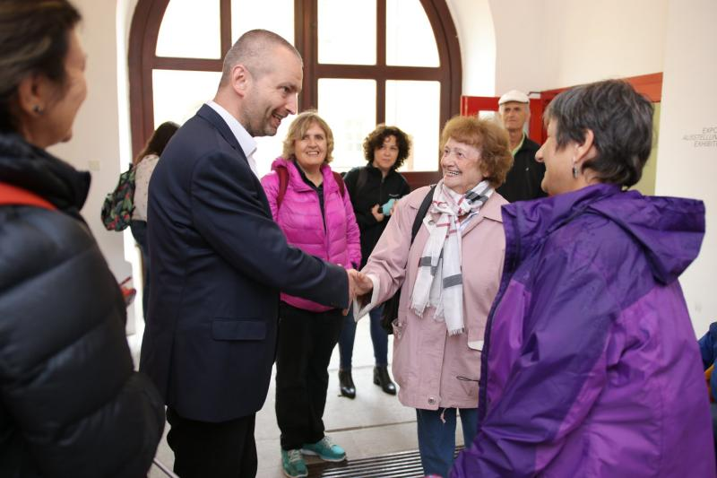 Employees of Beit Theresienstadt in the Terezín Memorial; pictured on the left is Mr. Jan Roubínek, Director of the Terezín Memorial, shaking hands with Mrs. Dita Krausová (center); on the right is Mrs. Tamy Kinberg, Director of Beit Theresienstadt. Photo: Radim Nytl, Terezín Memorial.